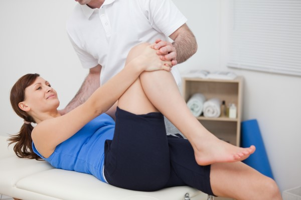 Brunette woman bending her leg while being accompanied by her doctor