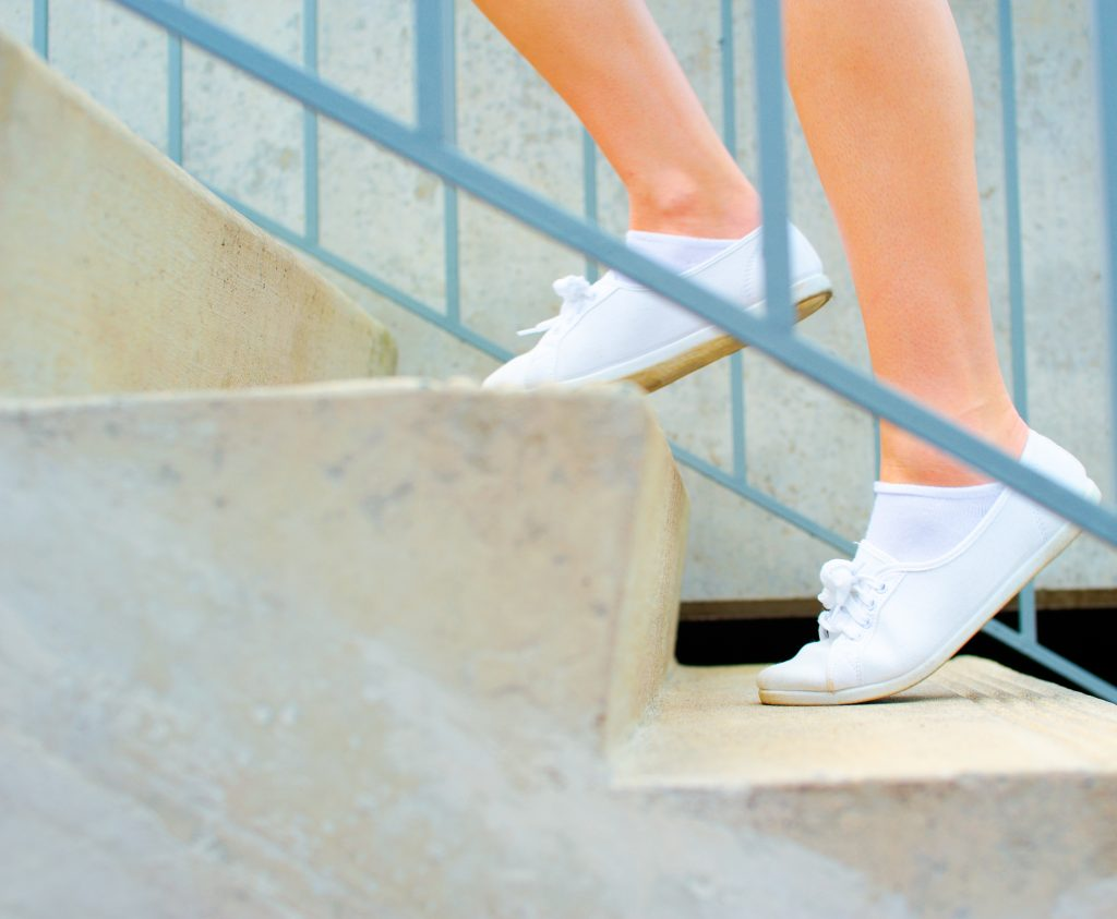 Feet In White Sneakers Climbing Stairs