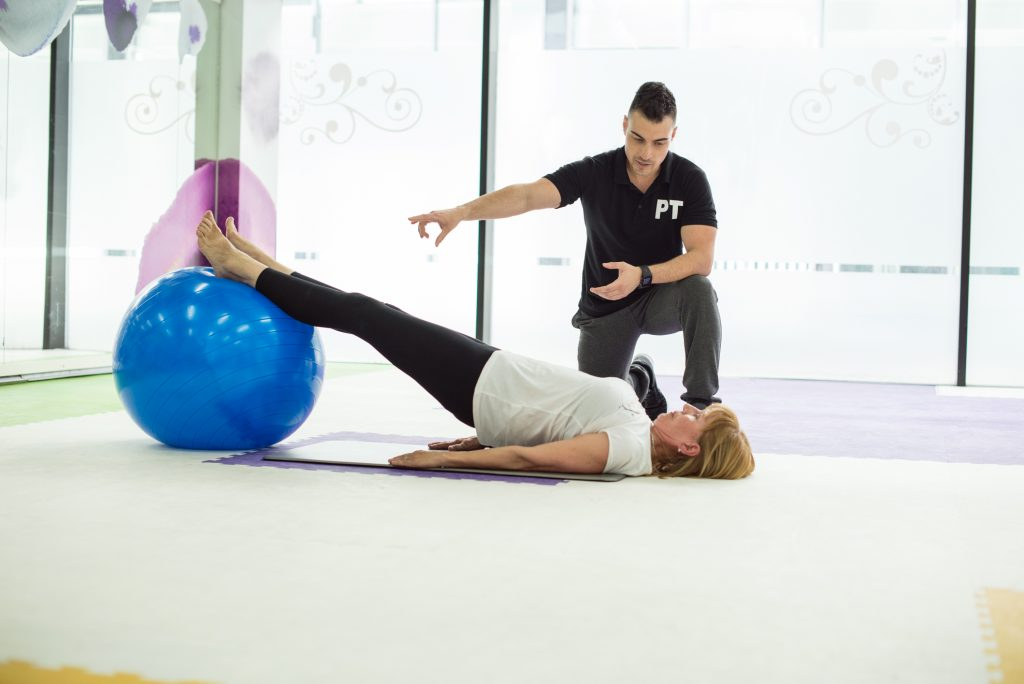 Physical Therapist And Lady With Feet Up On Exercise Ball