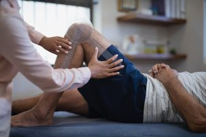 Person lying on a table with their knee bent as a physical therapist measures their knee and leg.