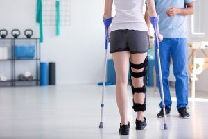 Person with crutches walking towards a Physical Therapist while in physical therapy.