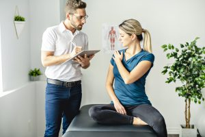 Woman with blonde hair holding her shoulder while speaking to a physical therapist.