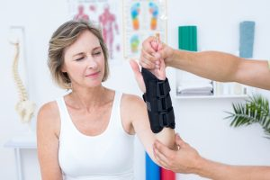 Photograph of a woman with an arm injury being looked at by a physical therapist.