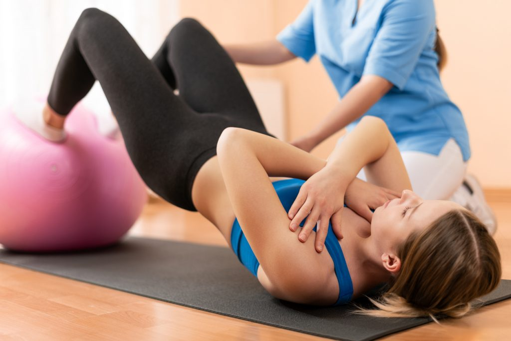 Physiotherapist Working with Female Client on Core Work