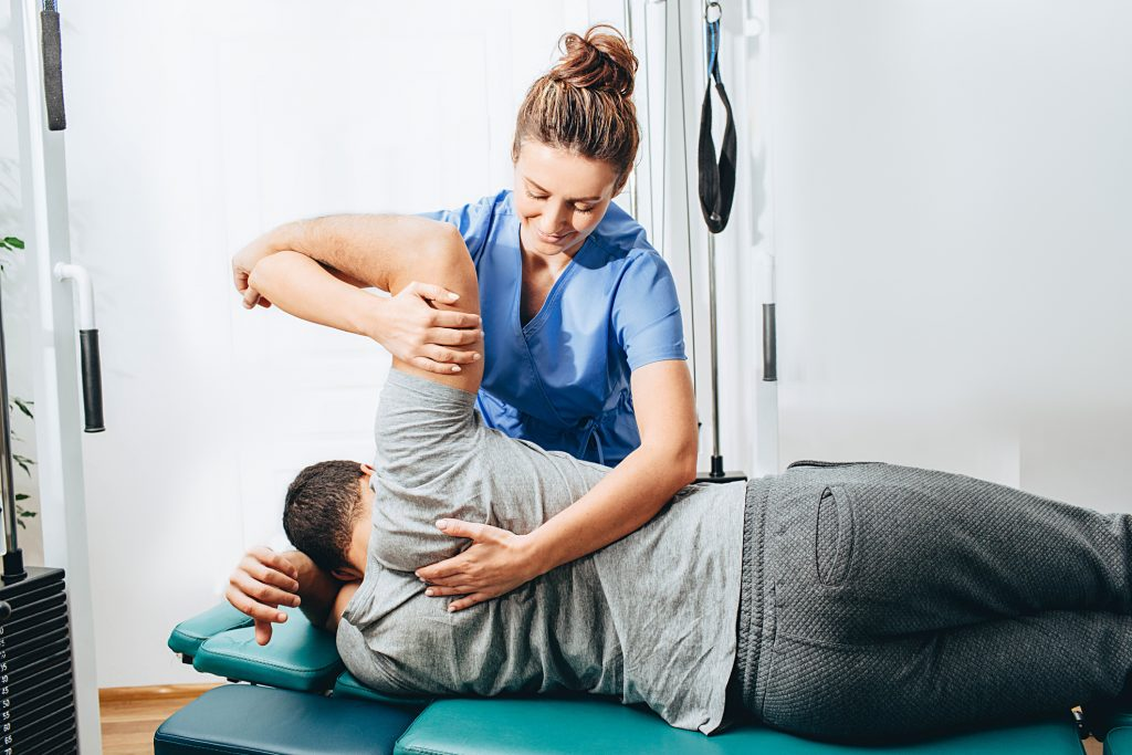 Physical Therapist Adjusting Patients Shoulder